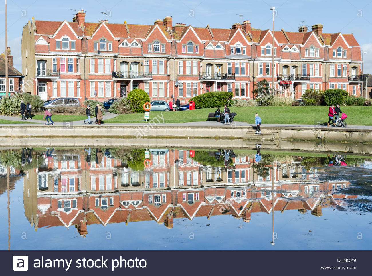 Victorian terraced houses with reflections in nearby lake. - Stock Image