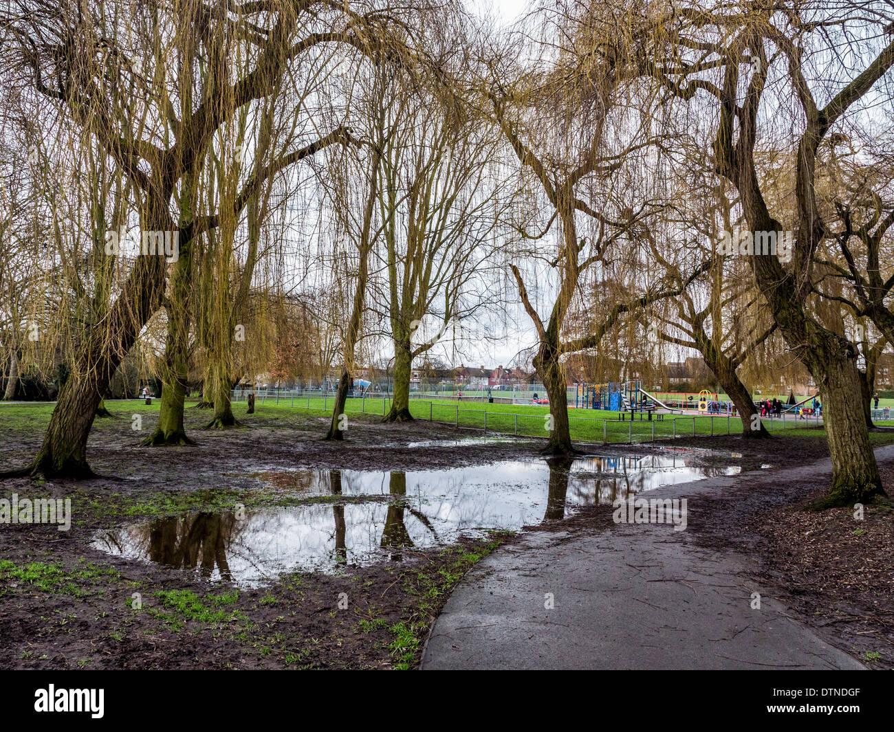 Crane Park - muddy puddles and standing water after heavy winter rainfall near Children's playground - Twickenham, UK - Stock Image