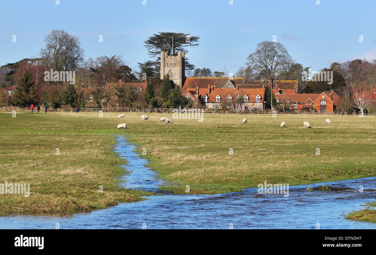 An English Rural Hamlet bathed in Winter sunshine with grazing Sheep and stream flowing through a water meadow - Stock Image