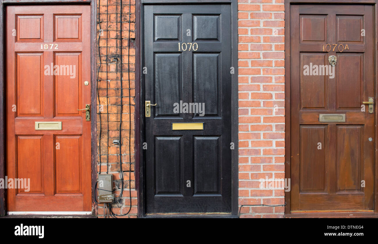 Three front doors on a row of flats and houses in Manchester Stock ...