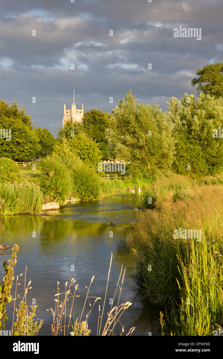 Evening sunlight illuminates Fairford Church and the River Coln in the Cotswolds, Gloucestershire, England. Summer (July) 2010. - Stock Image