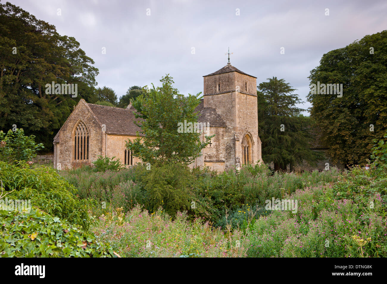 Eastleach Martin Church photographed from the verdant banks of the River Leach, The Cotswolds, Gloucestershire, England. - Stock Image