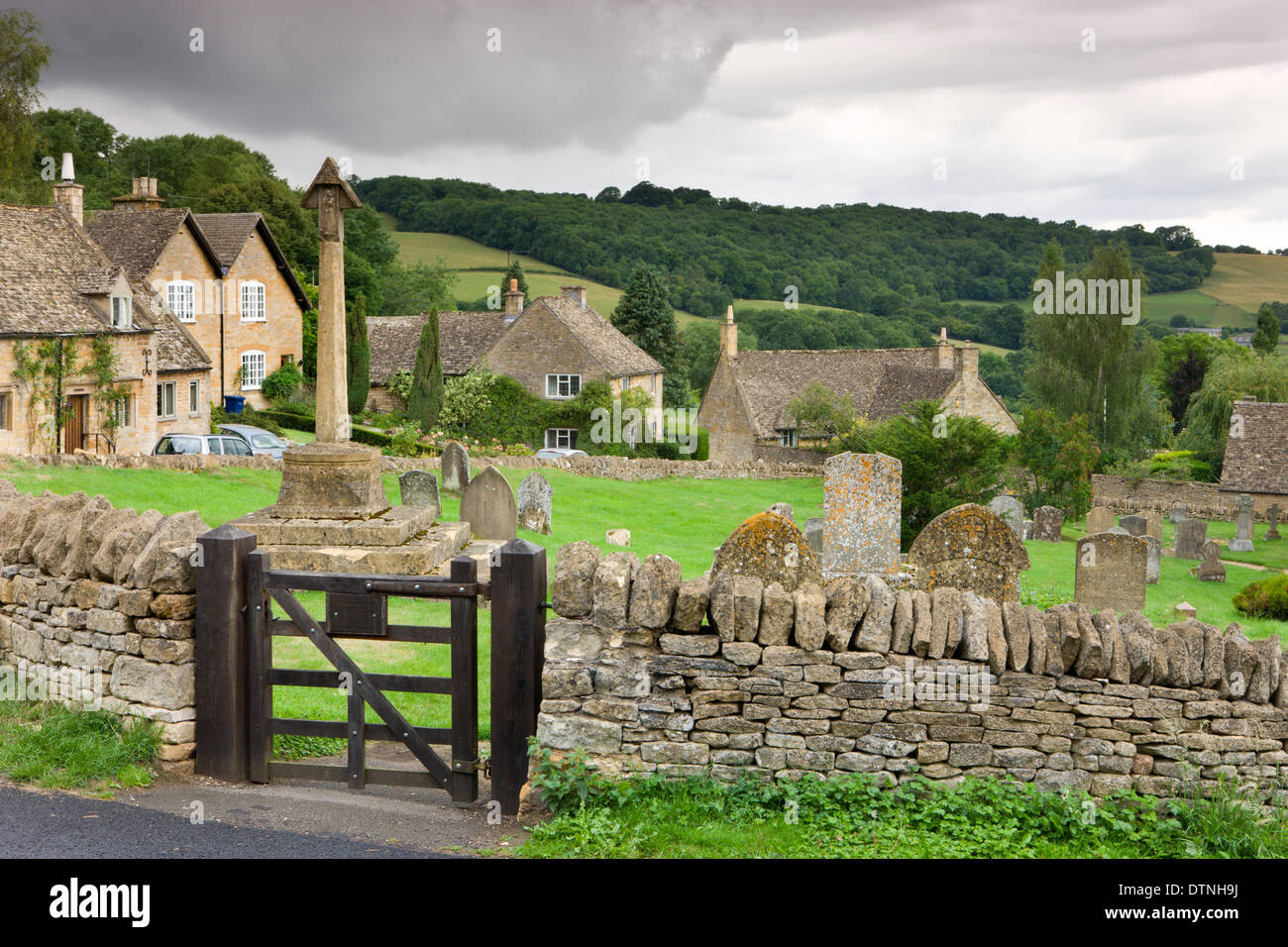 Graveyard and cottages in the pretty Cotswolds village of Snowshill, Worcestershire, England. Summer (July) 2010. - Stock Image