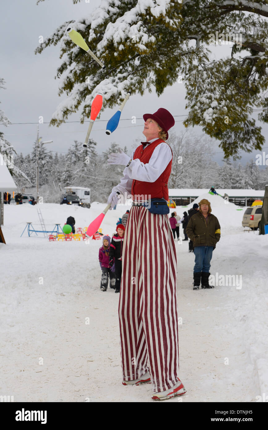 Clown man on stilts and top hat juggling pins in winter snow at the Marmora Snofest 2014 Ontario Canada - Stock Image