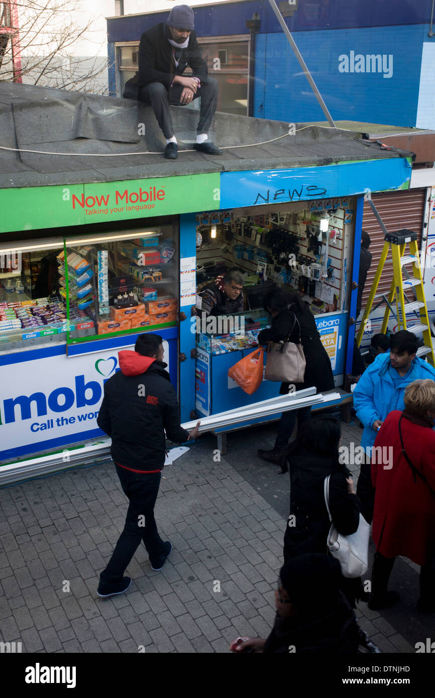 A man sits unnoticed on the roof of a mobile phone provider kiosk at Elephant & Castle in the south London borough - Stock Image