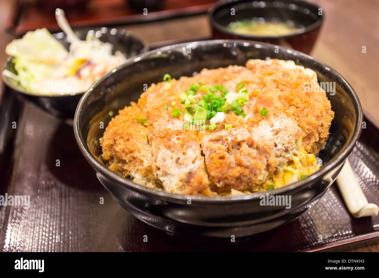 Katsudon - Japanese breaded deep fried pork cutlet (tonkatsu) topped with egg on steamed rice. - Stock Image