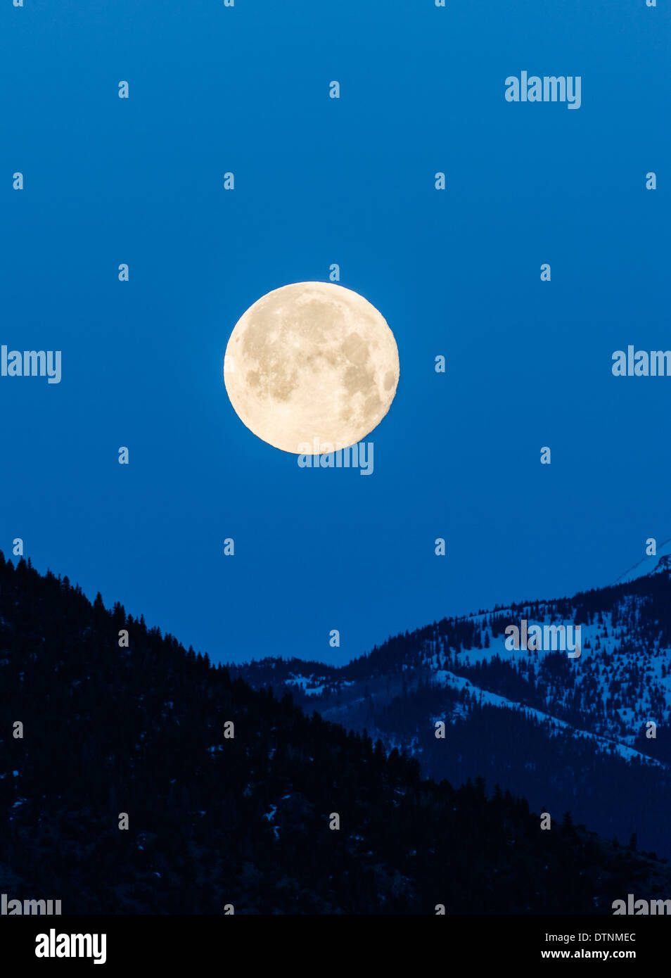 Full moon setting over Rocky Mountains, Salida, Colorado, USA - Stock Image