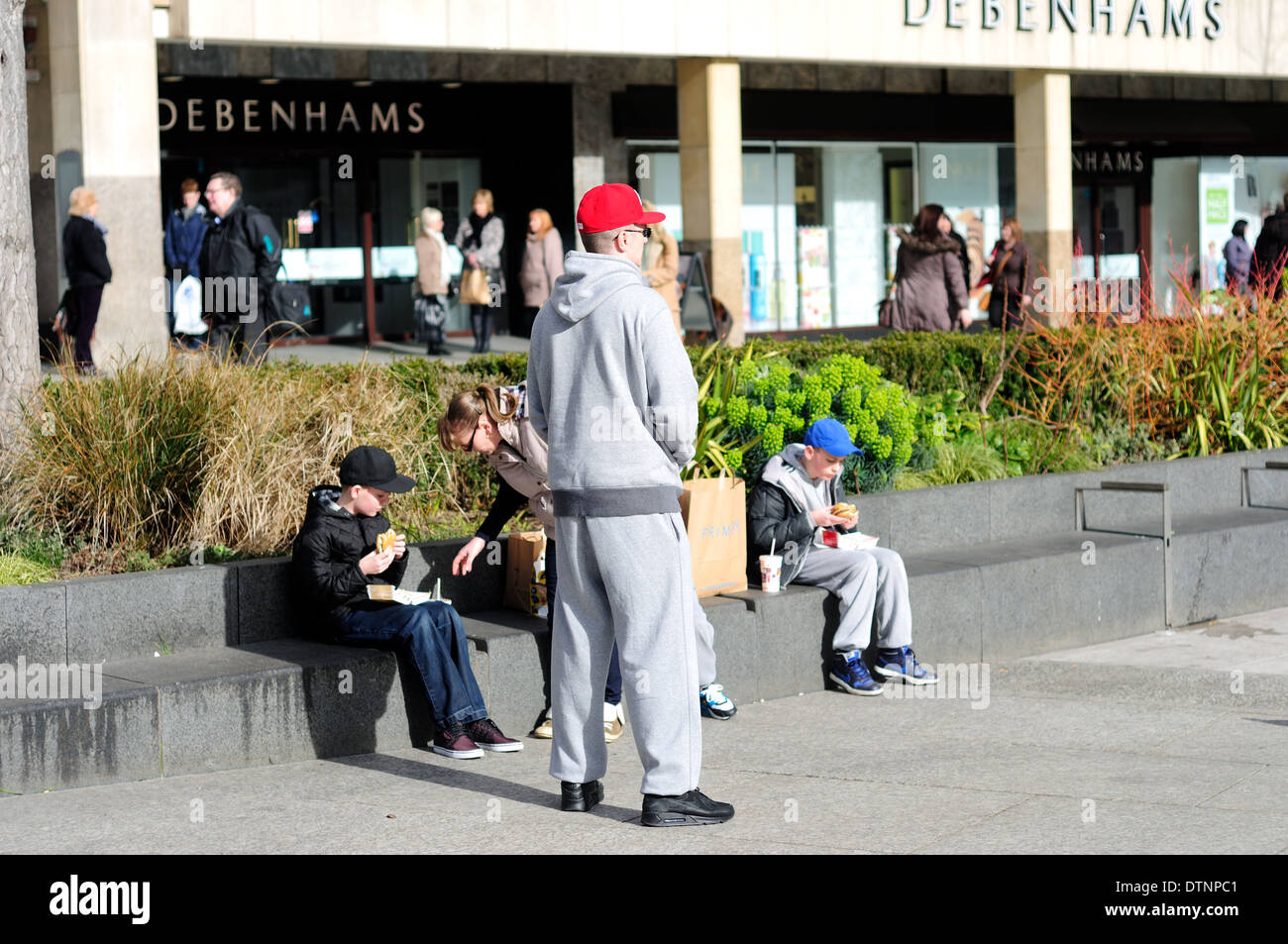 Nottingham market square ,Family eating fast food while sitting on wall. - Stock Image