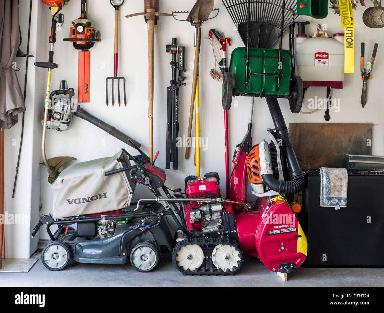 Garden tools and equipment inside residential garage - Stock Image
