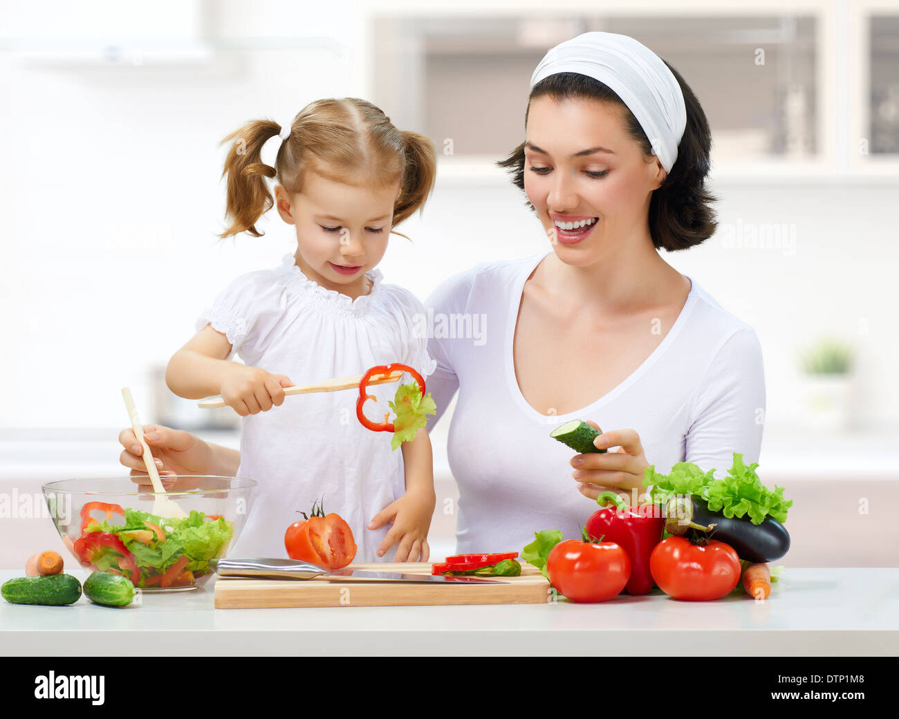mother and daughter prepare salads - Stock Image