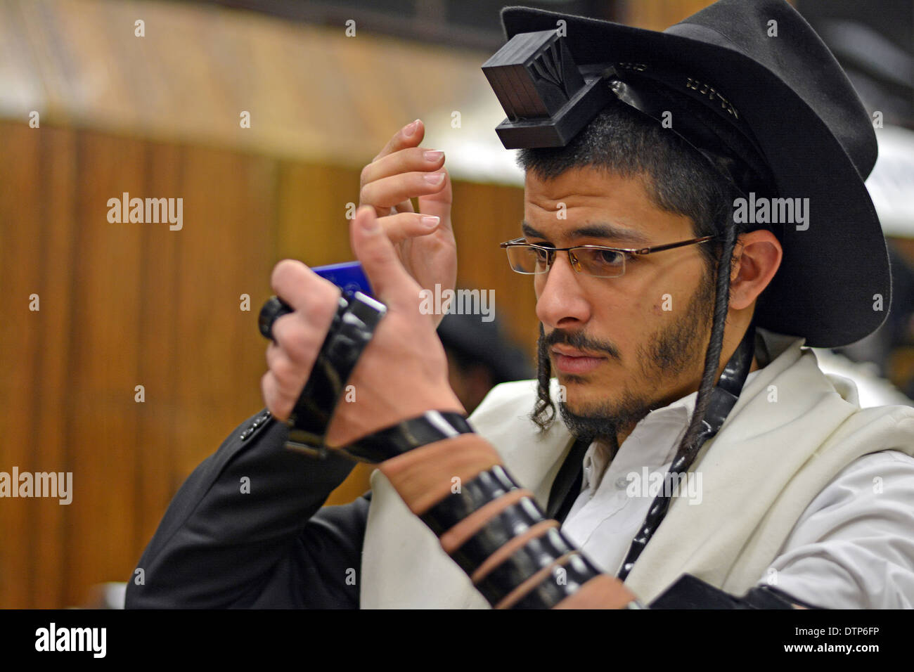 Using a small mirror a religious Jew adjusting his phylacteries at morning prayers at Lubavitch headquarters in Brooklyn - Stock Image