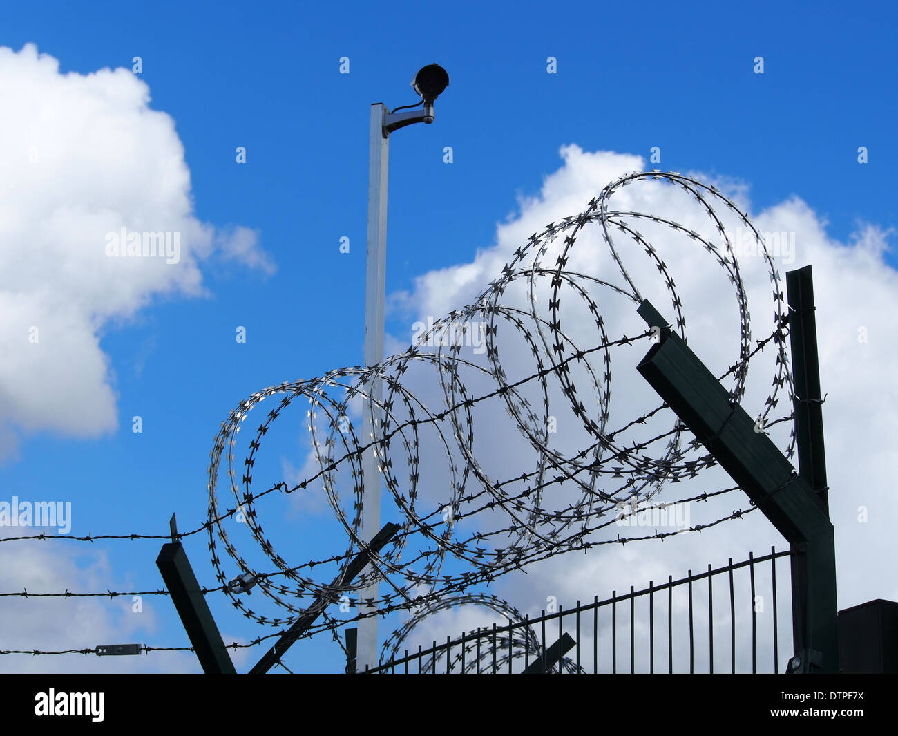 Restricted area - fence with barbed wire and camera - Stock Image