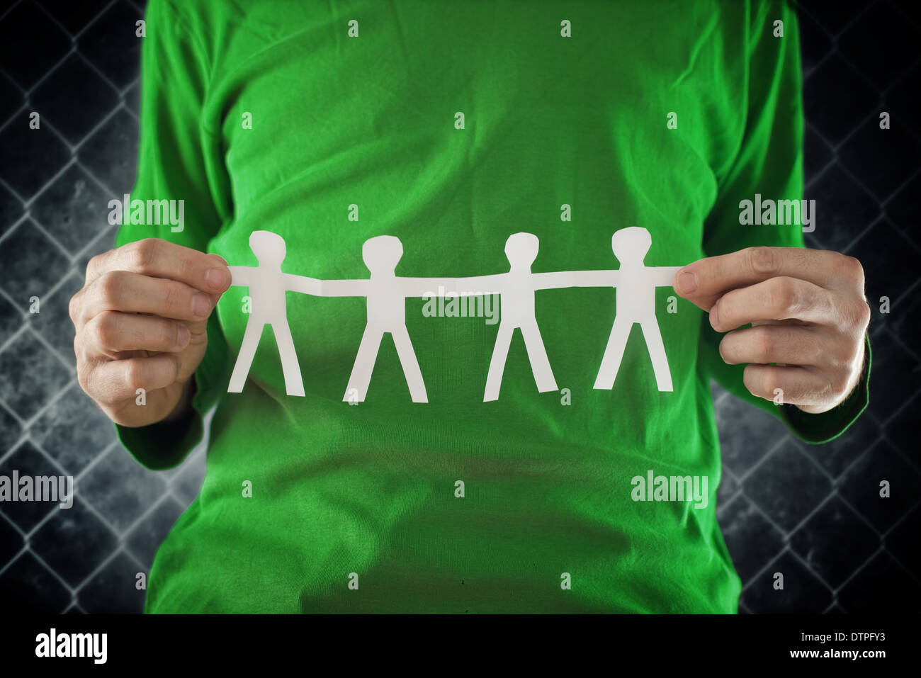 Man holding chain of people paper cuts, teamwork concept. Stock Photo