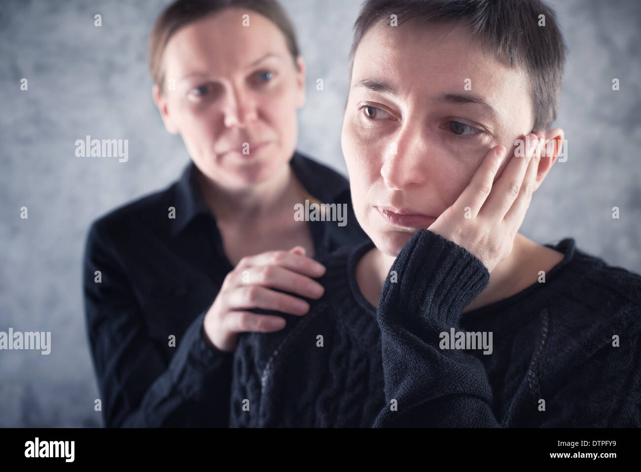 Comforting friend. Woman consoling her sad friend with hand on shoulder. - Stock Image