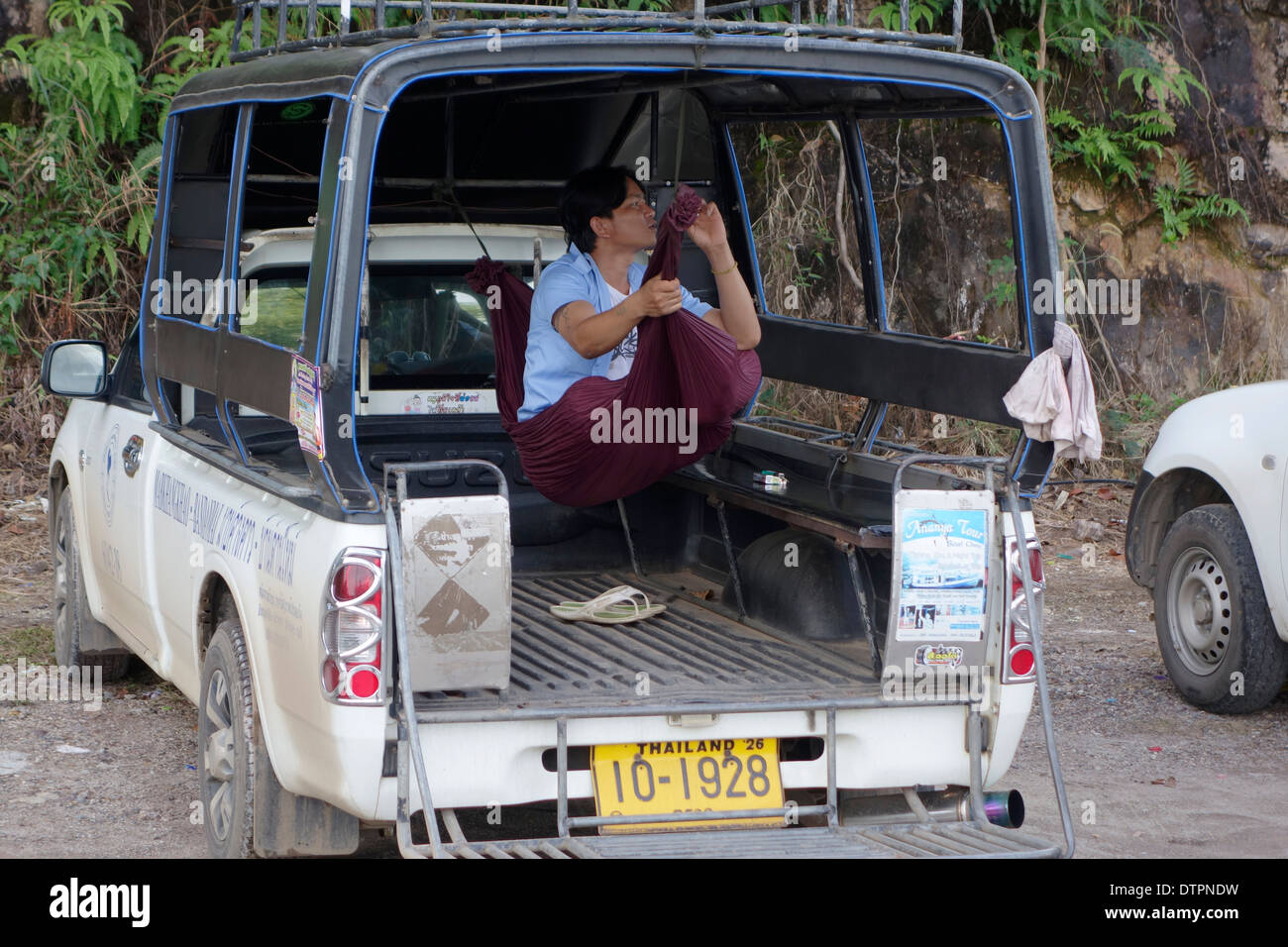 Songthaew driver resting on hammock, Koh Chang Island, Thailand. - Stock Image