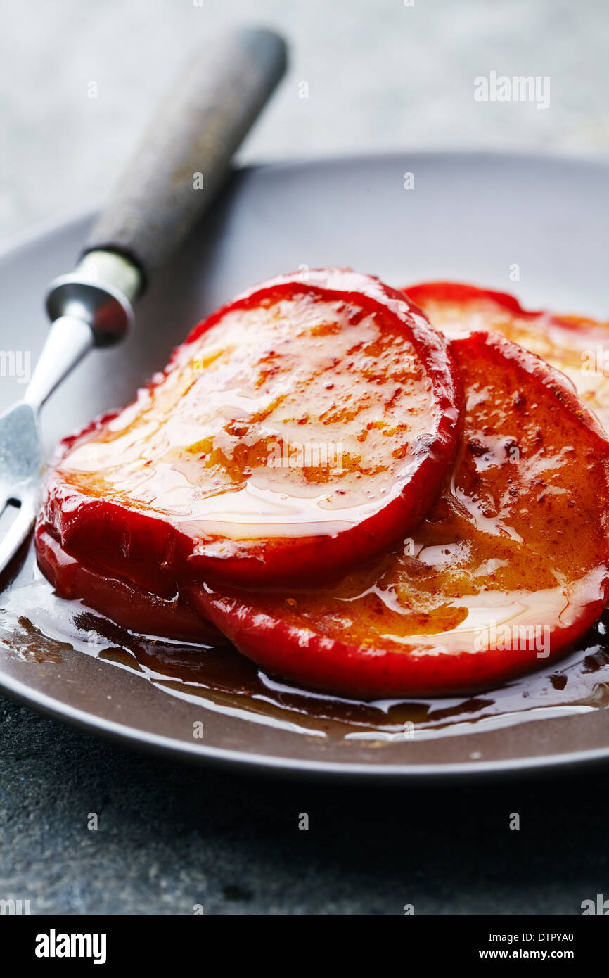 apples slices fried or baked in sugar, butter and cinnamon - Stock Image