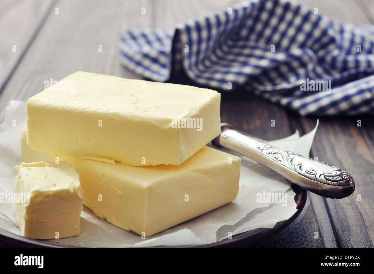 Fresh butter on wooden cutting board with knife closeup - Stock Image