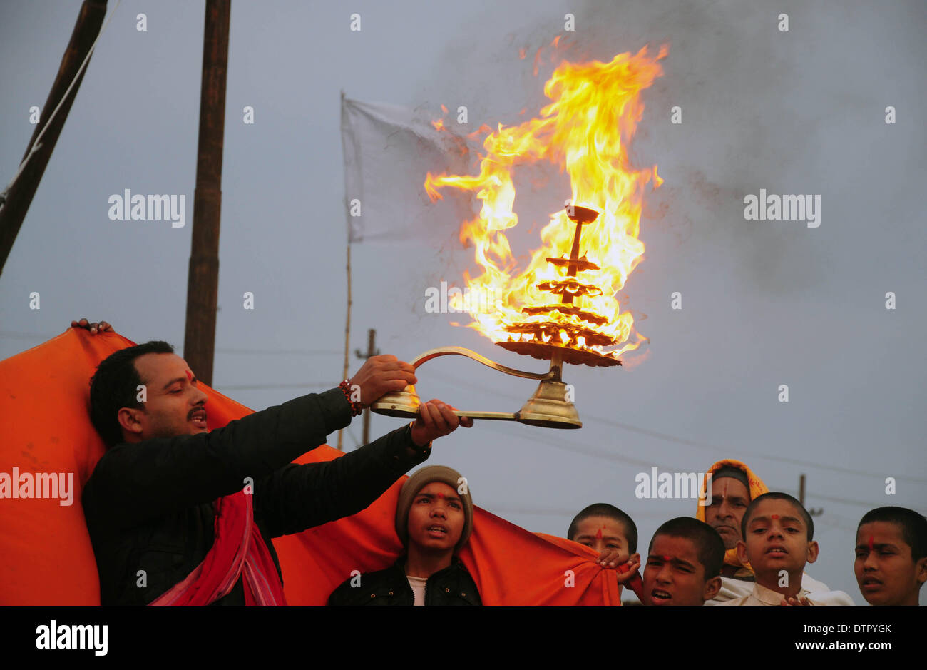 """Allahabad, India - 22--02-2014:  An Indian Hindu priest rotates a traditional oil lamp as he performs evening rituals at the Sangam, the confluence of the Rivers Ganges, Yamuna and mythical Saraswati during the annual traditional fair of """"Magh Mela"""" in Allahabad, India, Friday, Feb. 22, 2014. Hundreds of thousands of devout Hindus are expected to take holy dips at the confluence during the astronomically auspicious period of over 45 days celebrated as Magh Mela. Credit:  PACIFIC PRESS/Alamy Live News - Stock Image"""