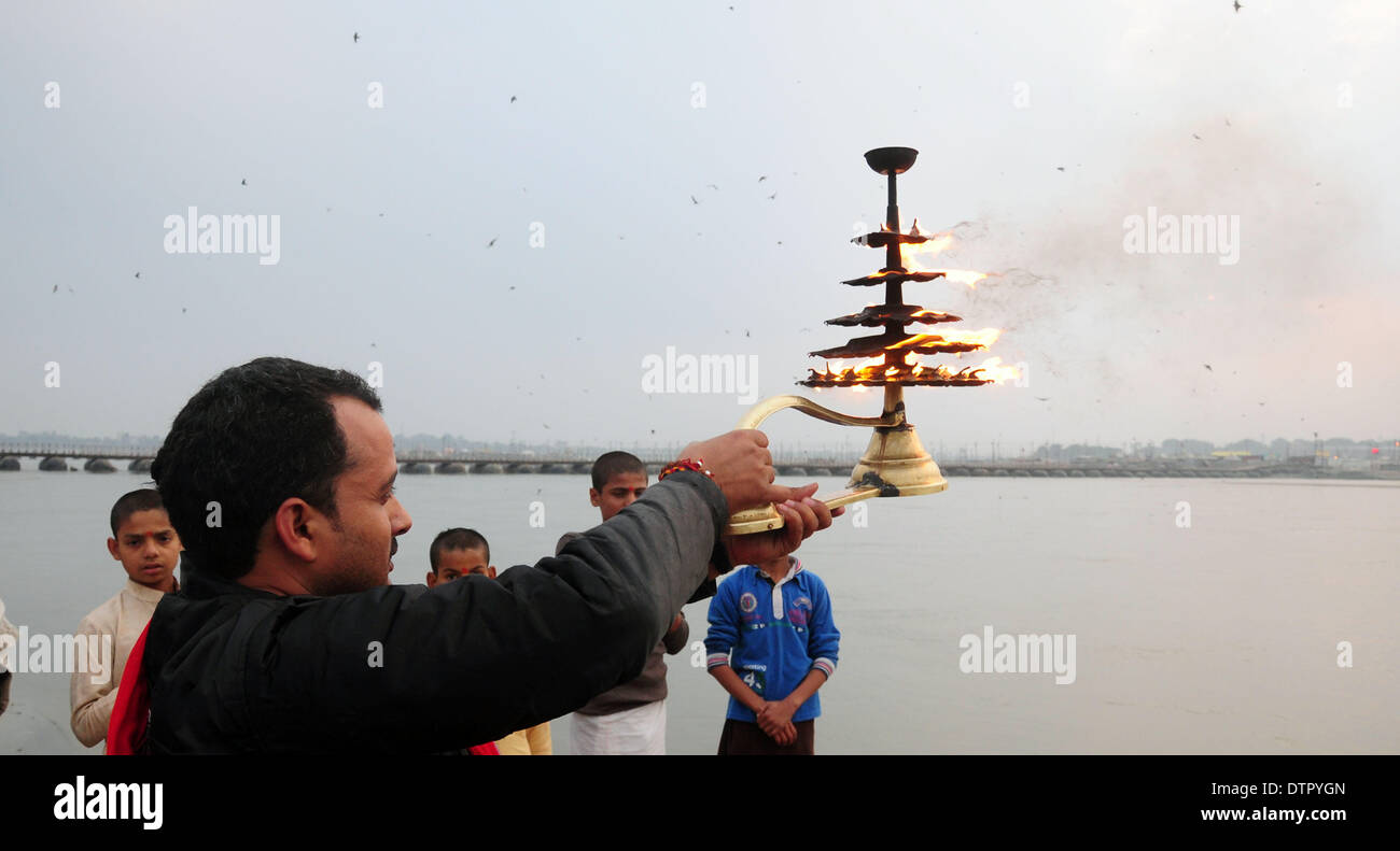 """Allahabad, India - 22--02-2014: An Indian Hindu priest rotates a traditional oil lamp as he performs evening rituals at the Sangam, the confluence of the Rivers Ganges, Yamuna and mythical Saraswati during the annual traditional fair of """"Magh Mela"""" in Allahabad, India. Hundreds of thousands of devout Hindus are expected to take holy dips at the confluence during the astronomically auspicious period of over 45 days celebrated as Magh Mela. Credit:  PACIFIC PRESS/Alamy Live News - Stock Image"""
