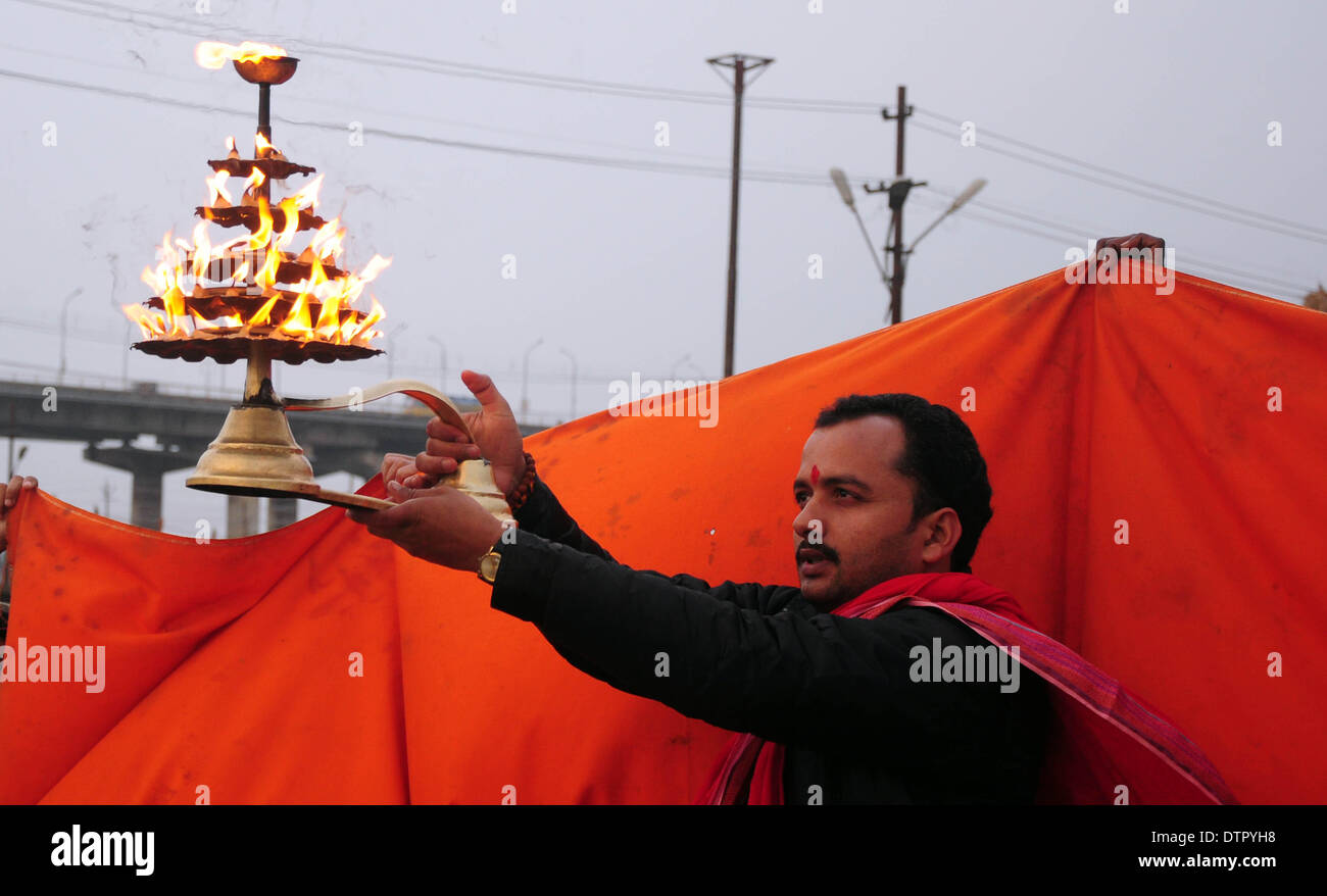 """Allahabad, India - 22--02-2014:  An Indian Hindu priest rotates a traditional oil lamp as he performs evening rituals at the Sangam, the confluence of the Rivers Ganges, Yamuna and mythical Saraswati during the annual traditional fair of """"Magh Mela"""" . Hundreds of thousands of devout Hindus are expected to take holy dips at the confluence during the astronomically auspicious period of over 45 days celebrated as Magh Mela. (Photo by Prabhat Kumar Verma/Pacific Press) Credit:  PACIFIC PRESS/Alamy Live News - Stock Image"""