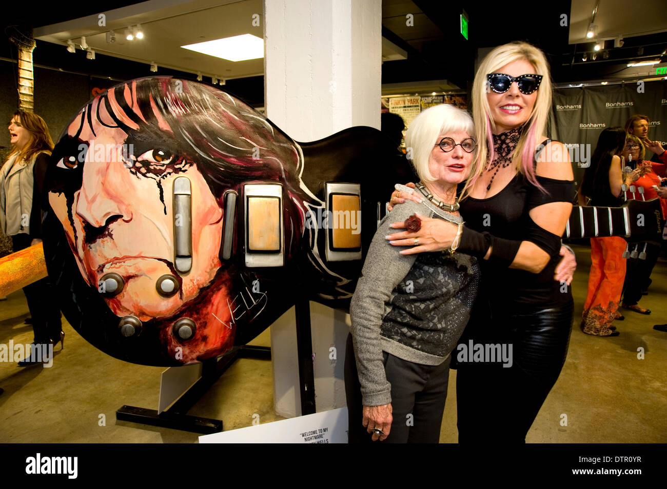 Hollywood, USA. 21st Feb, 2014. Gibson art guitar project contributor Stacey Wells( right) with Art Consultant Merry Norris (left) and  her creation of a guitar inspired by Alice Cooper.The art guitars were displayed on the Sunset Strip for a year and then auctioned off at Bonham's with the proceeds going to charity. Credit:  Robert Landau/Alamy Live News - Stock Image