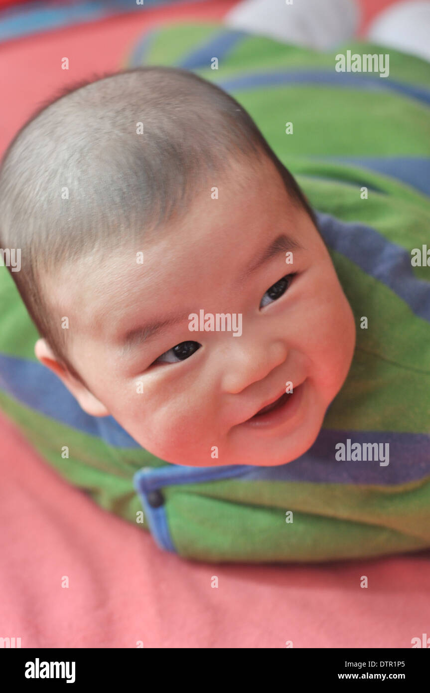 lovely asian baby crawling on bed - Stock Image