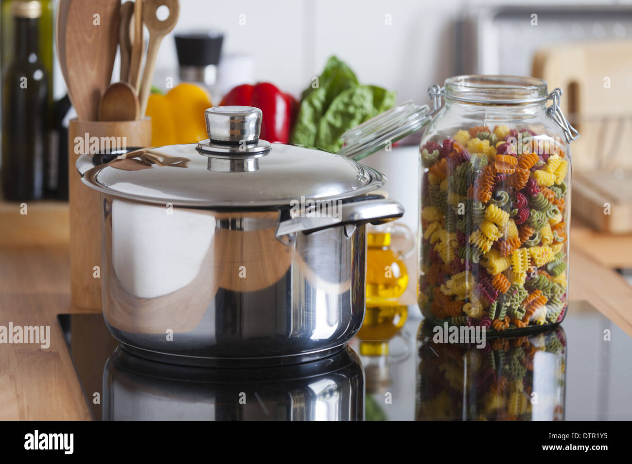 Cooking Pot and a Storage Jar with colorful Pasta with Copy Space in the upper and lower Area of the Image - Stock Image