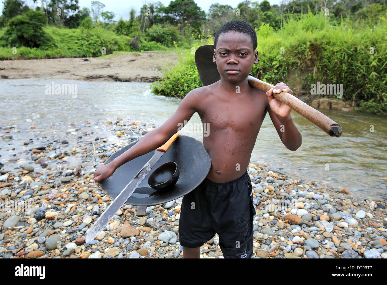 Gold digger boy with pan, shovel and machete in a river, Choco Province, Columbia, South America - Stock Image