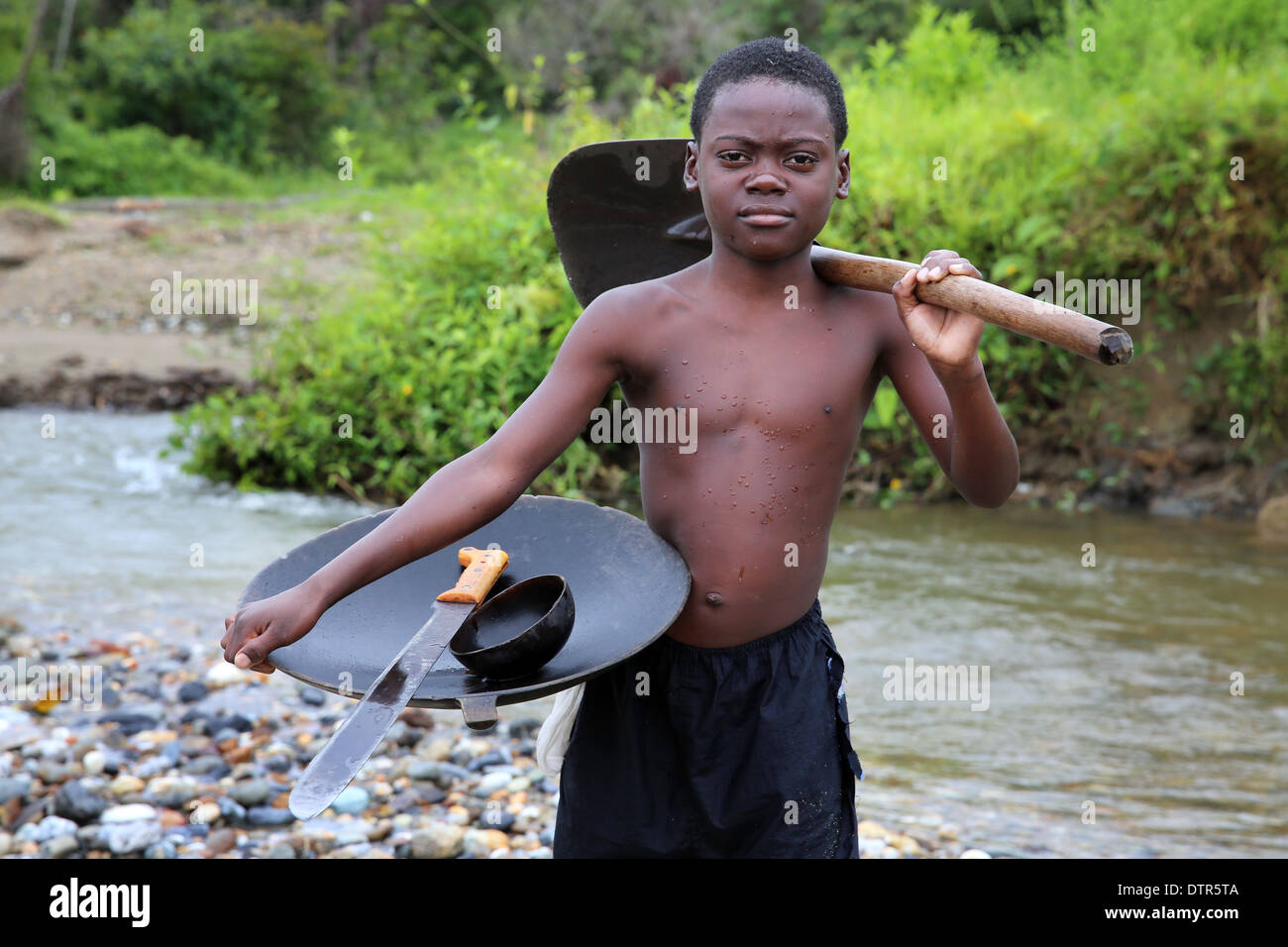 Gold digger boy with pan, shovel and machete in a river, Choco Province, Columbia, South America Stock Photo