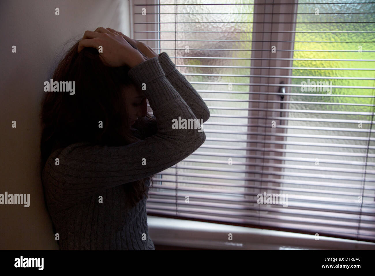 Unrecognizable young female with her hands on her head by a window. - Stock Image