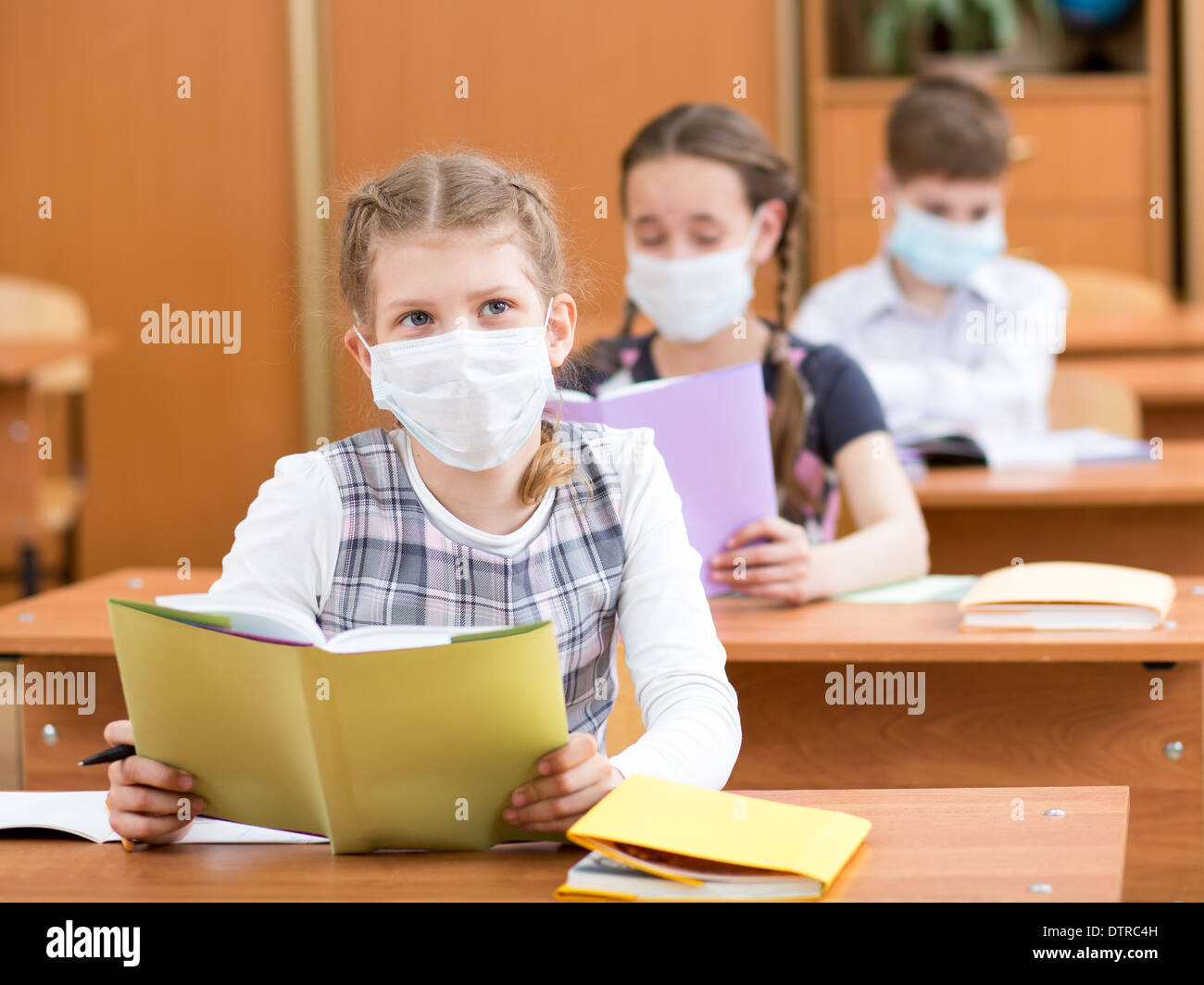 school kids with protection mask against flu virus at lesson - Stock Image