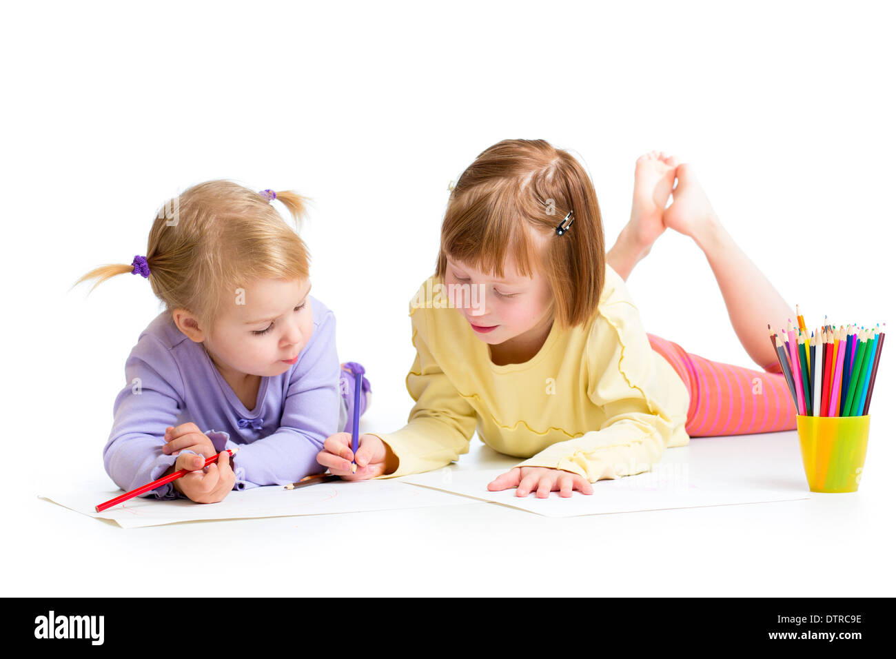 two girls drawing with color pencils together over white - Stock Image