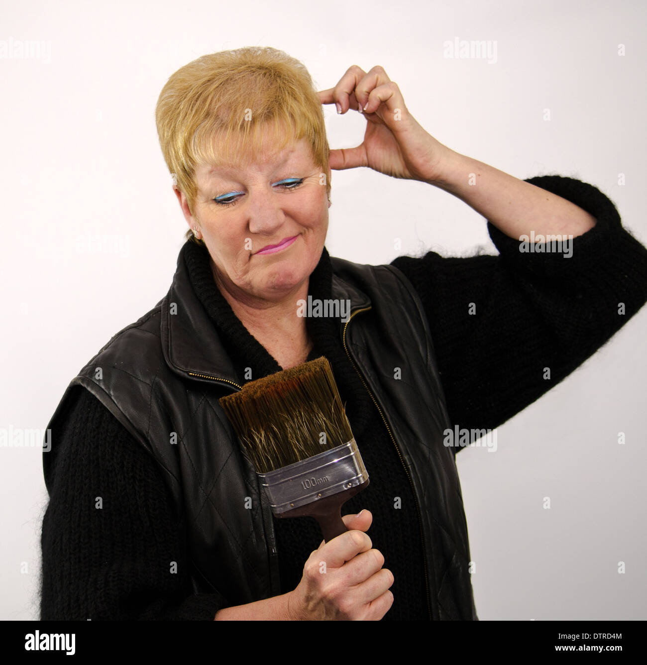 Blonde haired woman looking puzzled with paint brush - Stock Image