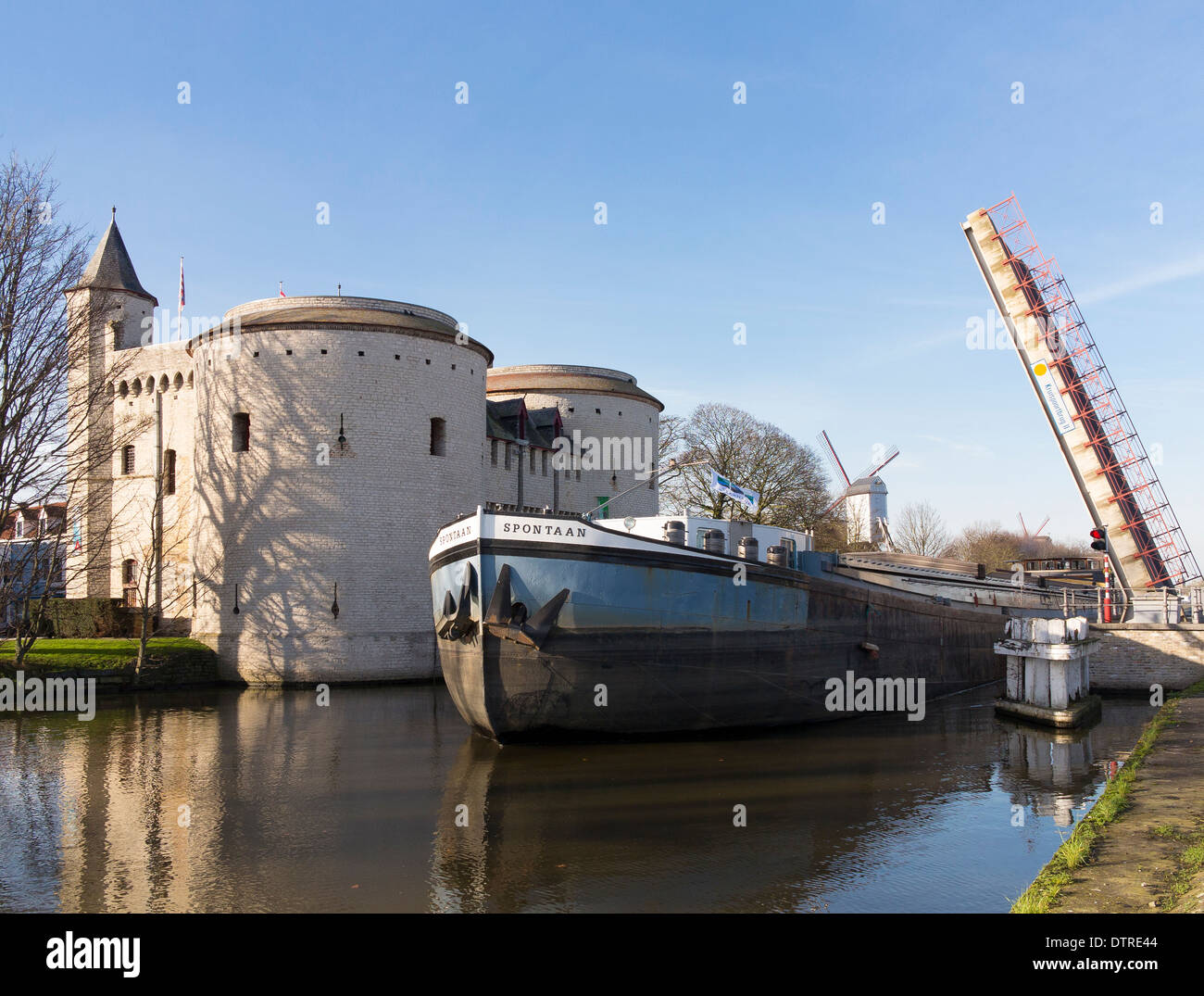 A freight carrying barge on the canal around Bruges city centre at the Kruispoort gate (Brugge) - Stock Image