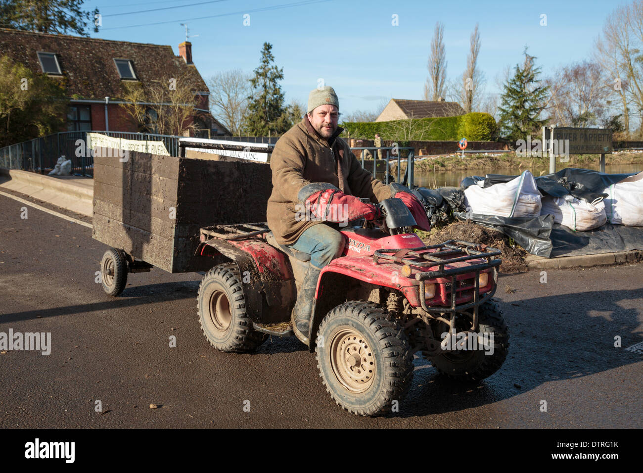 Pub landlord Jim Winkworth uses a quad bike with trailer to deliver supplies and rescue animals from the heavy floods at Burrowbridge on February 22, 2014. As landlord of the King Alfred Inn, he has also been at risk of flooding but has been helping his locals with errands throughout the crisis, visiting local villages of Moorland and Fordgate by travelling along the banks of the River Parrett. - Stock Image