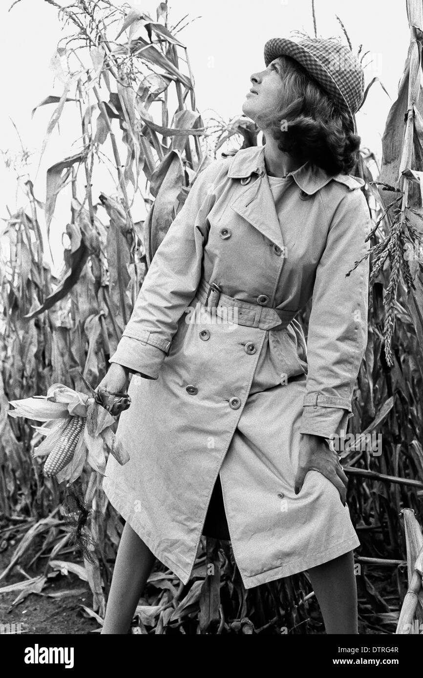 Sixties fashion model with raincoat and hat posing in a maize field - Stock Image