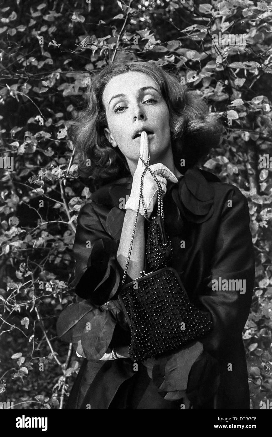Sixties fashion model portrait with black coat and handbags - Stock Image