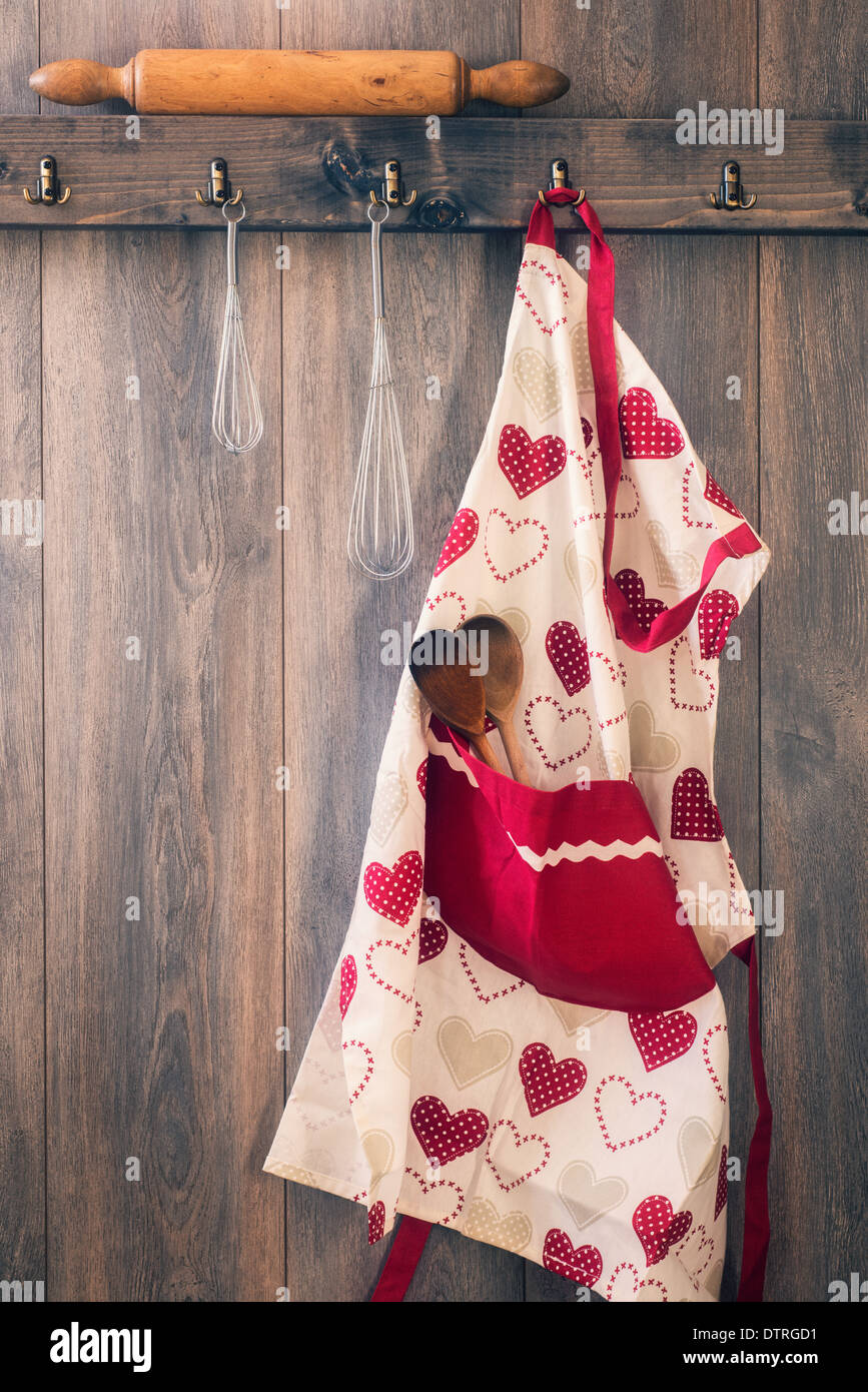 Apron hanging on hook in kitchen with utensils - vintage tone effect - Stock Image
