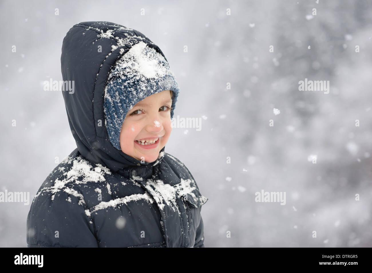 Happy Child in Wintertime snowflakes around - Stock Image