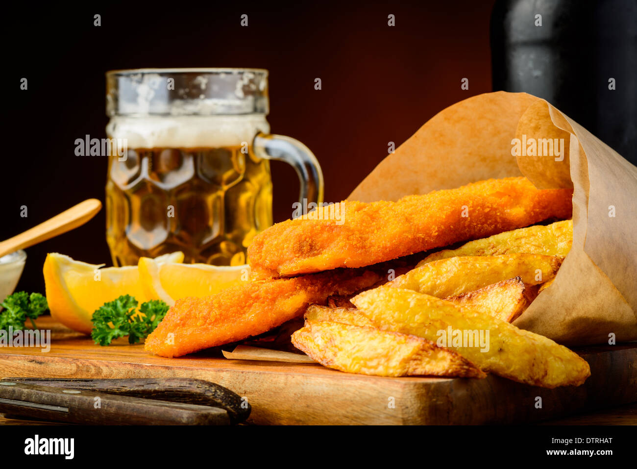 still life with fish and chips meal and glass of beer - Stock Image