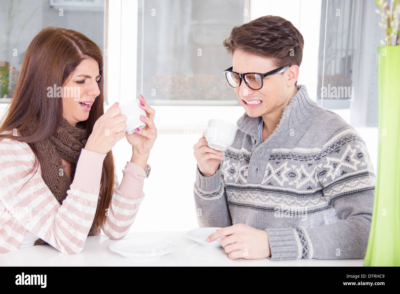 young pretty couple having unpleasant taste from the cup indoor - Stock Image