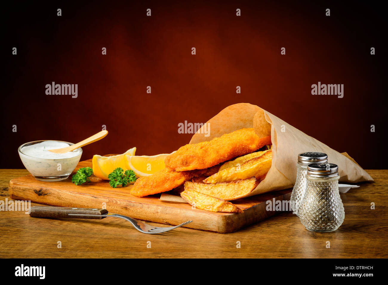 delicious traditional fish and chips meal with lemons and dip - Stock Image