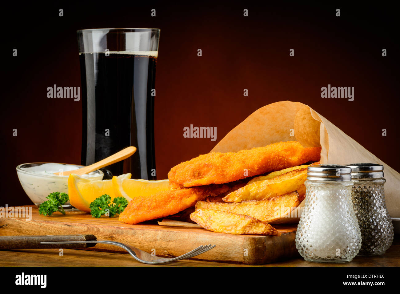 traditional fish and chips wrapped in paper with cola drink - Stock Image