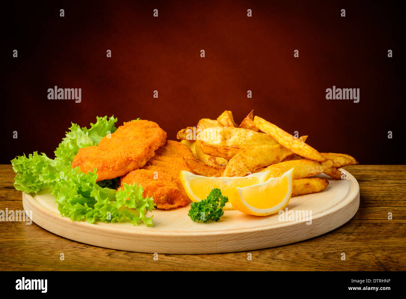 still life with traditional fish and chips, lemons, on a wooden plate - Stock Image