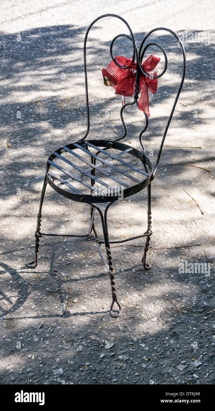 fanciful wire frame chair decorated with big red bow serves serving as humorous parking place saver outside boutique Oaxaca - Stock Image