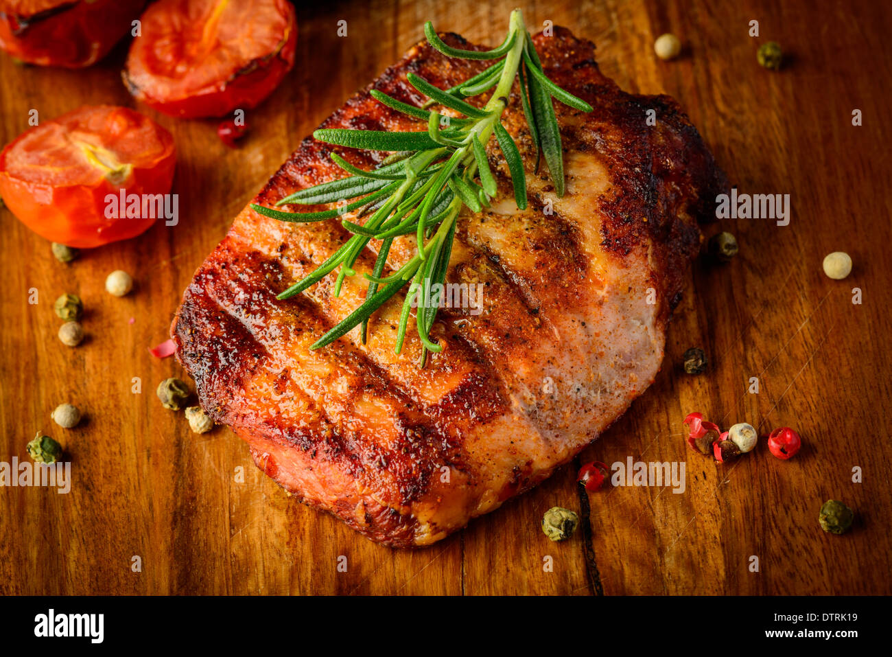 closeup detail of grilled meat steak with spices and rosemary on a wooden plate Stock Photo