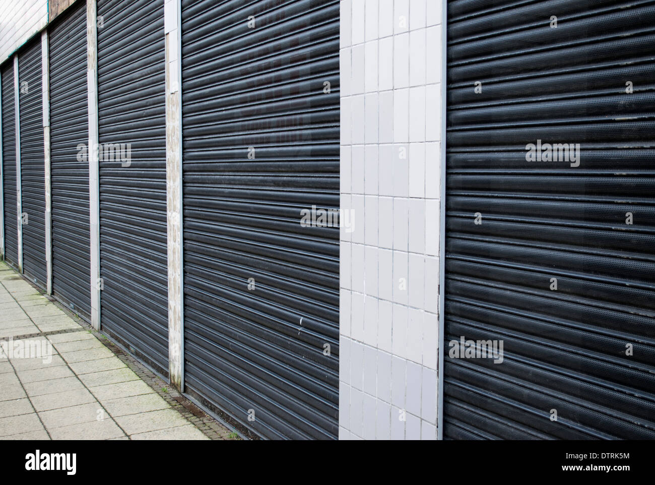 Detail of closed metal shutters on a shop front in the UK highlighting the impact of recession and economic downturn Stock Photo