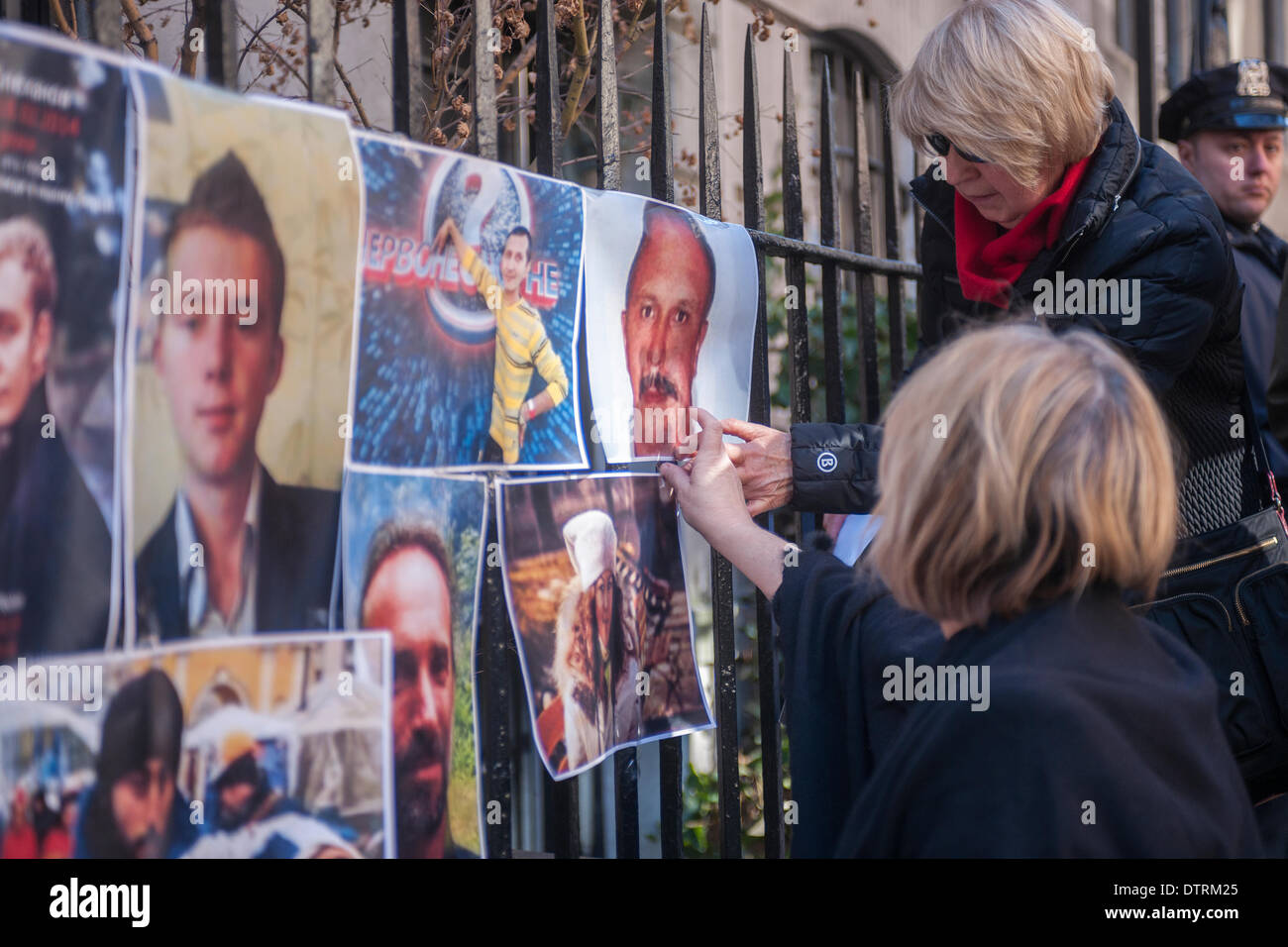 New York, USA. 23rd Feb, 2014. Ukrainian-Americans paste photographs of their fallen brethren in front of the Ukrainian Stock Photo