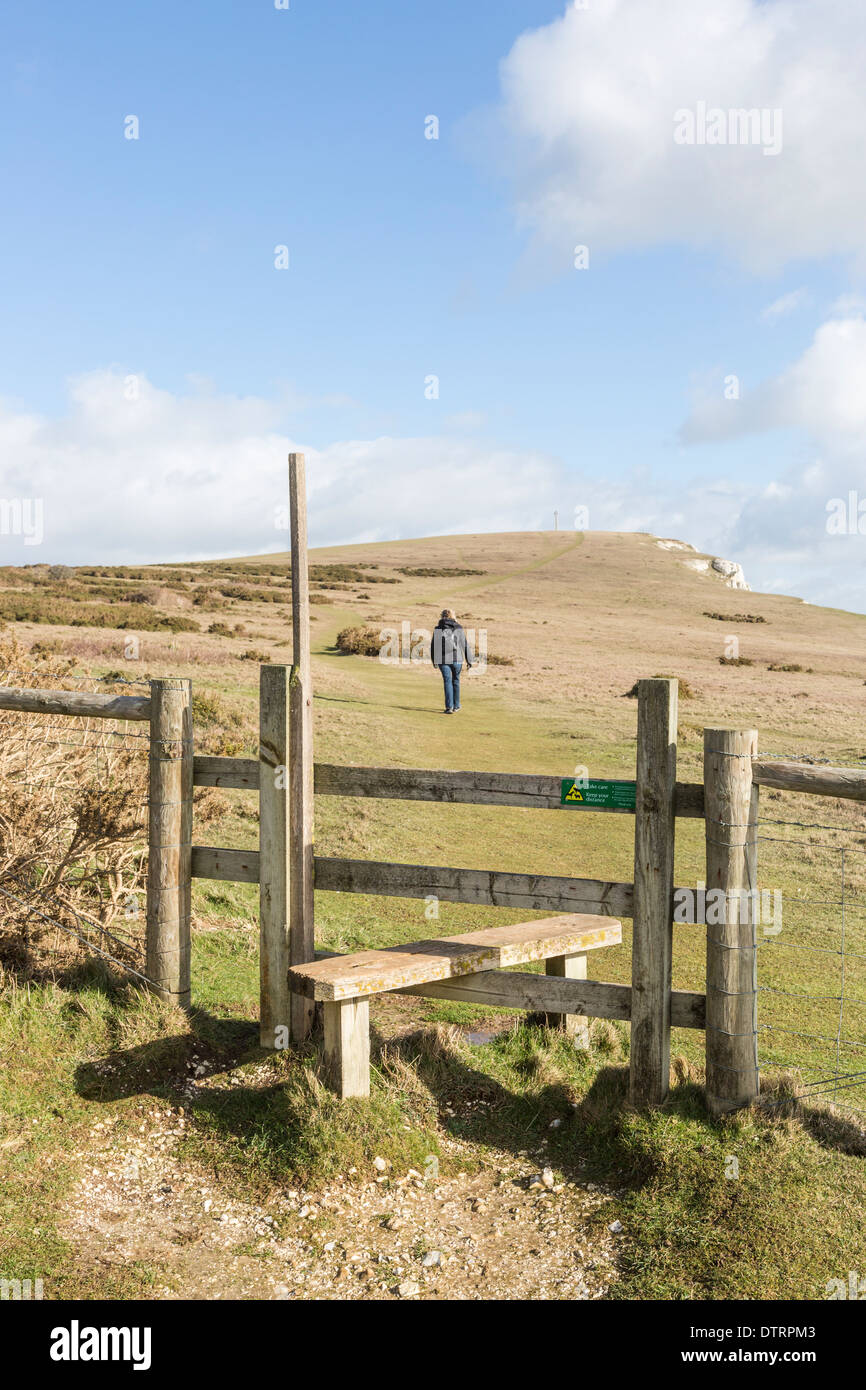 Wooden stile at Tennyson Down, chalk downland at The Needles Country Park, Isle of Wight, UK in good weather, blue sky, clouds - Stock Image