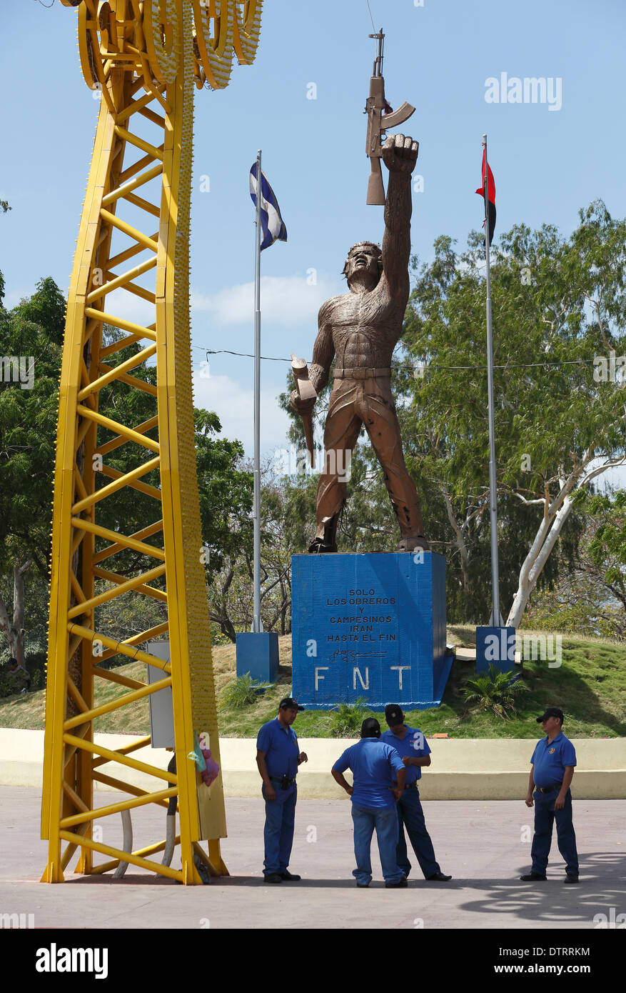 Revolutionary statue and men from the ruling FSLN party, Managua Nicaragua - Stock Image